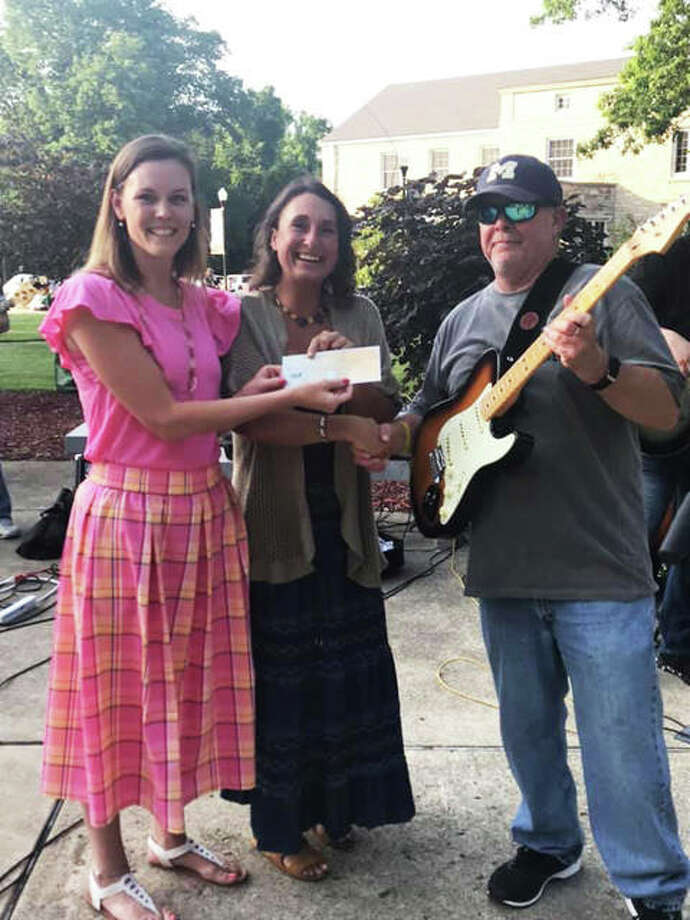 Upper Alton Association President Jamie Ruyle, left, presents Alton Main Street Executive Director Sara McGibany, middle, with a check for downtown Alton flood relief and beautification during last Tuesday's Rockin' with Robert concert. Musician Bud Summers, right, performed before the event's biggest crowd to date and suggested funds generated from a drawing go toward the effort. Photo: Courtesy Of Upper Alton Association