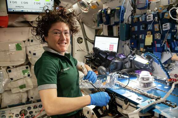 In this April 25, 2019 photo, NASA astronaut Christina Koch is shown working on space botany research using the Veggie PONDS gear to cultivate and harvest lettuce and Mizuna greens for consumption on the International Space Station and analysis on Earth.