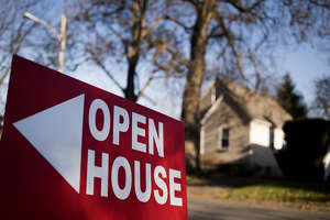 """An """"Open House"""" sign is displayed in the front yard of a home for sale in Columbus, Ohio, on Dec. 3, 2017."""