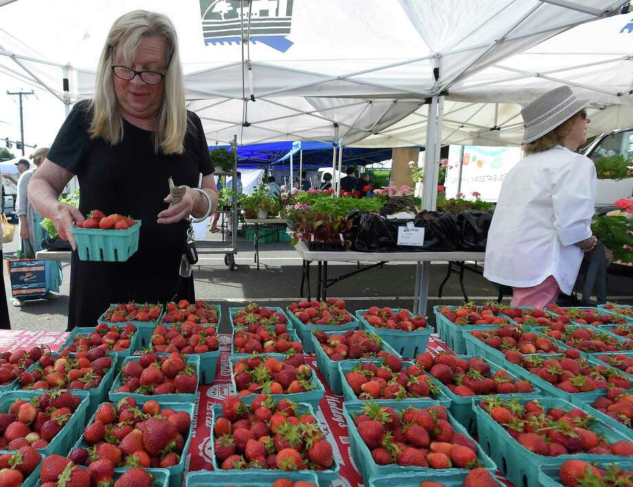 Lynne Carriello of Greenwich picks up some fresh strawberries from the Plasko Farm stand at the Greenwich Farmers Market in the Arch Street Commuter Lot on June 8, 2019 Greenwich, Connecticut. Carriello, a longtime customer of the market, will make jams and preserves from the fresh fruit. Photo: File / Matthew Brown / Hearst Connecticut Media / Stamford Advocate