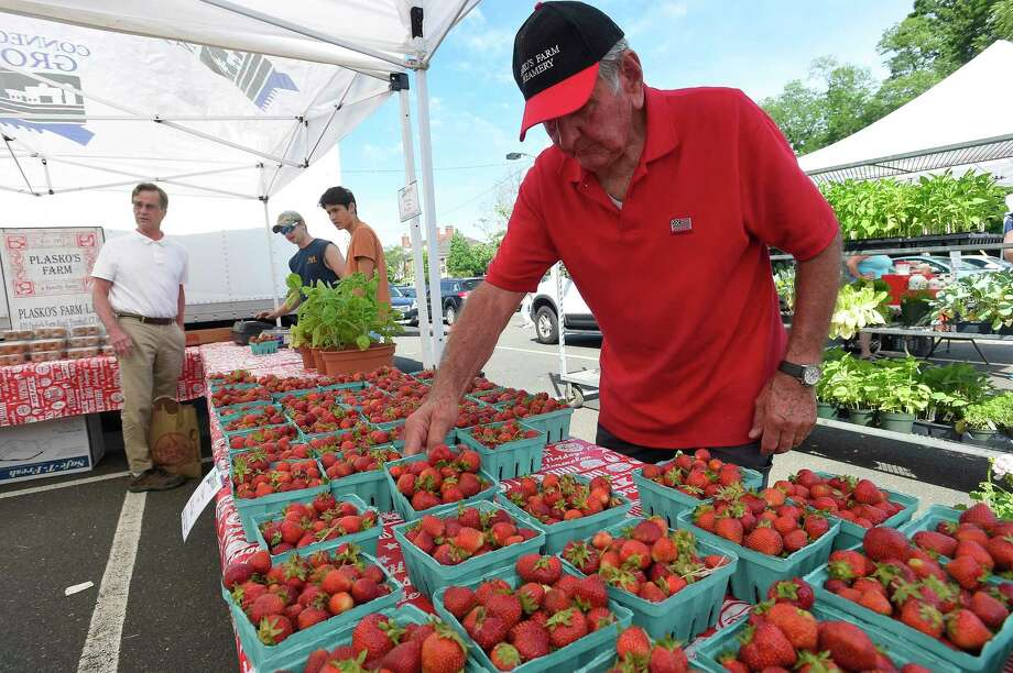 John Plasko of Trumbull, has been selling fruits and vegetables at the Greenwich Farmers Market in the Arch Street Commuter Lot for the pasts 22 years. Plasko straigtens up quart containers of freshly picked strawberries on June 8, 019 Greenwich, Connecticut. Photo: Matthew Brown / Hearst Connecticut Media / Stamford Advocate