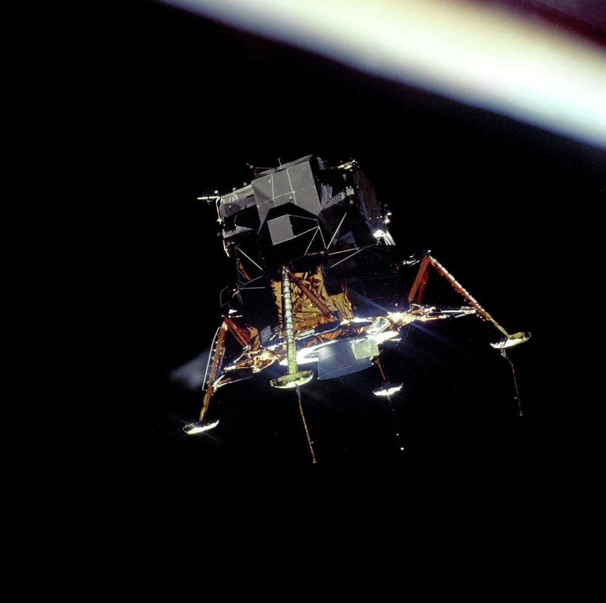 """The Apollo 11 Lunar Module Eagle, in a landing configuration, was photographed in lunar orbit from the Command and Service Module Columbia. """"The Eagle has landed"""" was spoken when the module landed on the lunar surface."""