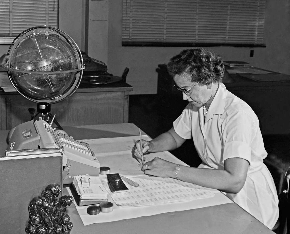 """NASA research mathematician Katherine Johnson photographed at her desk at NASA Langley Research Center with a globe, or """"Celestial Training Device,"""" in 1962."""