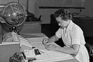 "NASA research mathematician Katherine Johnson photographed at her desk at NASA Langley Research Center with a globe, or ""Celestial Training Device,"" in 1962."