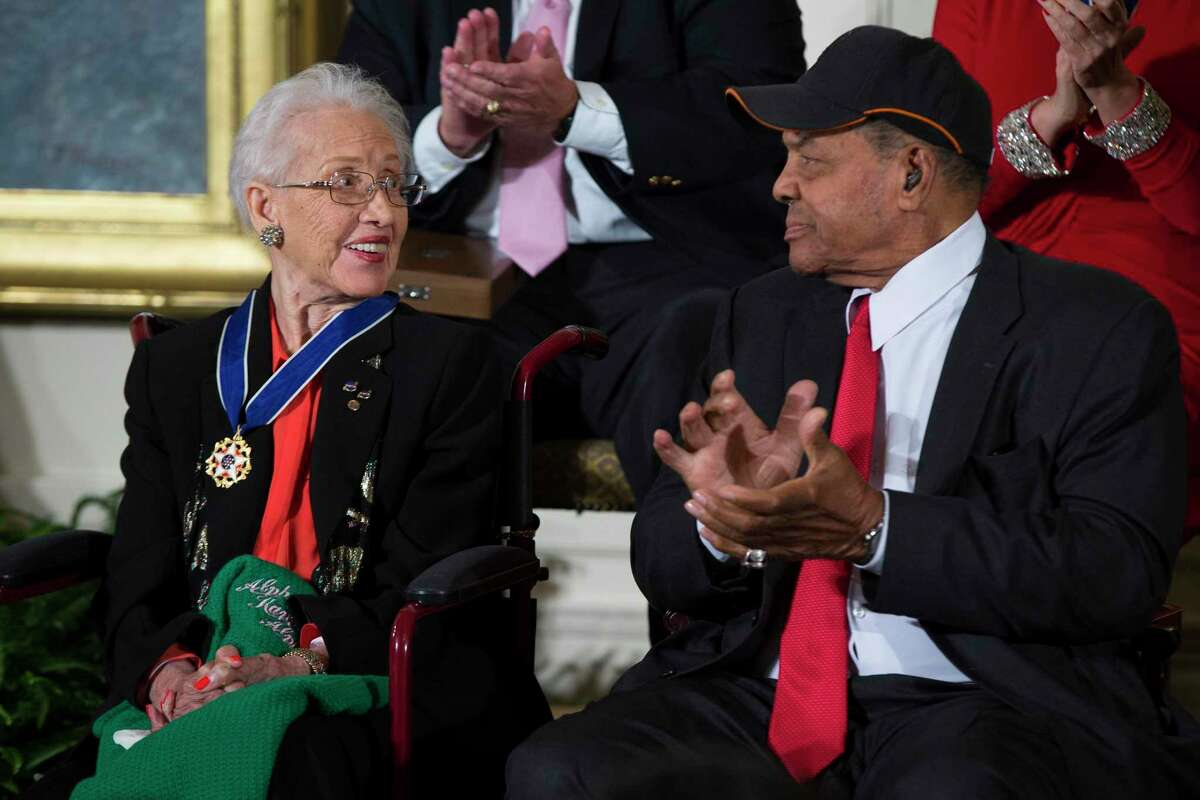 In this Nov. 24, 2015, file photo, baseball legend Willie Mays, right, applauds NASA mathematician Katherine Johnson, after she received the Presidential Medal of Freedom from President Barack Obama during a ceremony in the East Room of the White House.