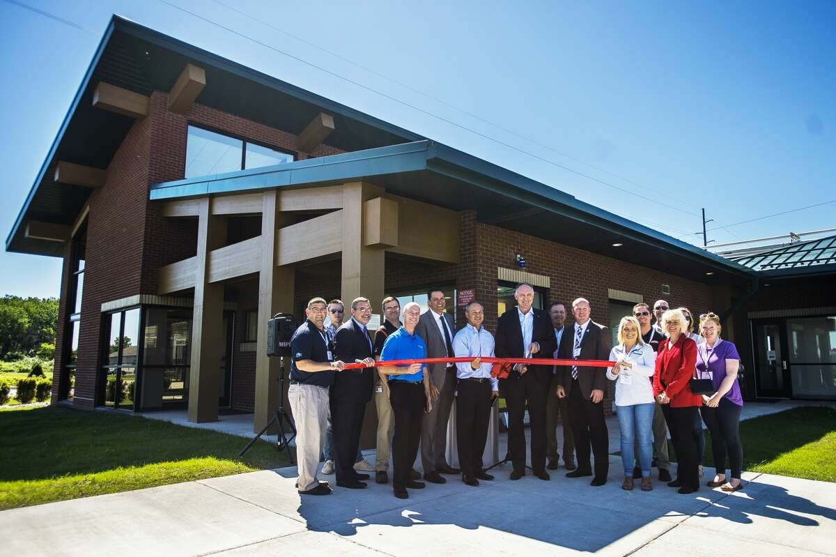 Site leaders from Cabot Corporation, Corteva Agriscience, Dow, DuPont, SK Saran and Trinseo, along with members of the Midland Business Alliance, pose for a photo during a ribbon cutting event for the Michigan Operations I-Park's new gatehouse entrance on Thursday, June 20, 2019 in Midland. (Katy Kildee/kkildee@mdn.net)