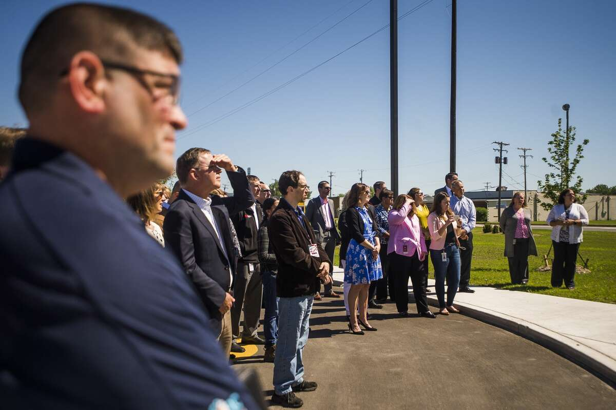 Guests listen as Dow Vice President of Operations, Canada and USA North Reiner Roghmann speaks during a ribbon cutting event for the Michigan Operations I-Park's new gatehouse entrance on Thursday, June 20, 2019 in Midland. (Katy Kildee/kkildee@mdn.net)