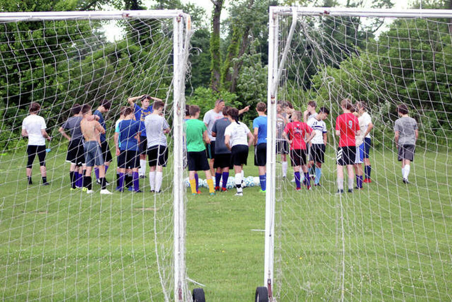 Civic Memorial High School boys soccer coach Derek Jarmen, center, is framed by a pair of portable soccer goals as he explains the next drill to players during a summer workout session Thursday at the Bethalto Sports Complex. Photo: Pete Hayes | The Telegraph