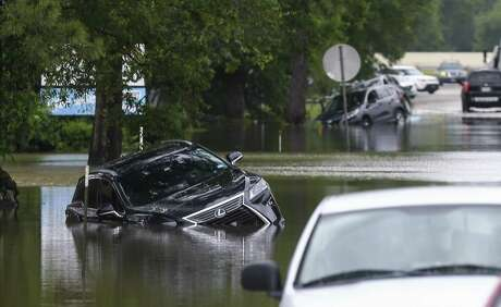 Vehicles remain stuck in the flooded E. Knox Drive following an overnight storm Wednesday, May 8, 2019, in Porter, Texas.