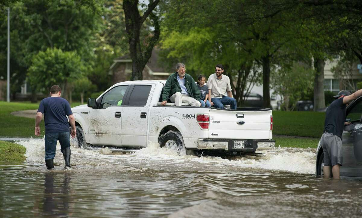 Residents drive down Austin Parkway across Sweetwater Boulevard in the Colony Bend neighborhood of Sugar Land, Texas, on Wednesday, May 8, 2019. Residents have been surprised that the water has not receded more quickly as it has in the past when the rain has stopped. In a video released Wednesday morning, the mayor of Sugar Land told residents that levees to the Brazos River had been closed, and that water was now being pumped over the levees into the Brazos, making the water recede much more slowly. More rain is forecast for the coming days.