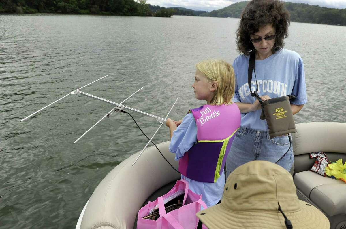 Kylie Martus, 9, holds an antena, for Theodora Pinou, a biology teacher at Western Connecticut State University Tuesday, August 2, 2016 on Candlewood Lake. A team of researchers use an antena to detect the frequency assosciated with various sterile grass carp released in June. This will help them track the movement of the fish throughout Candlewood Lake. Photo Tuesday, August 2, 2016.