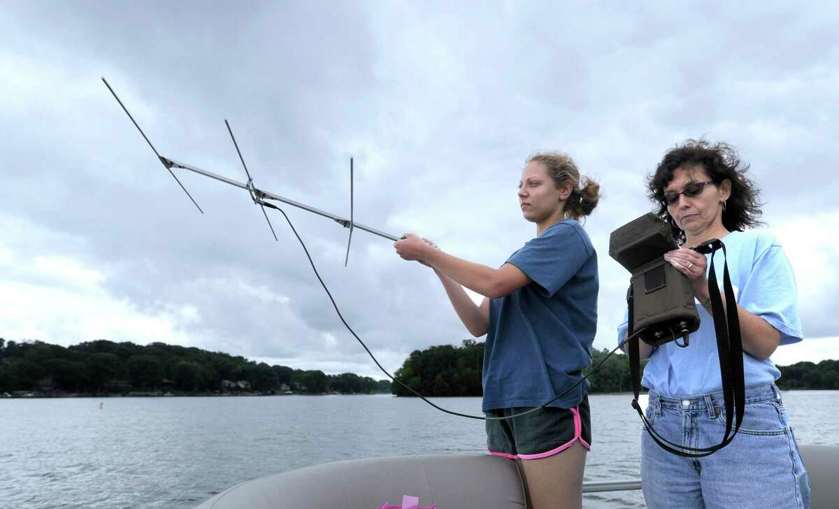 Michelle Bissett, left, an intern at the Great Hollow Wilderson School, and Theodora Pinou, a bioloy professor at Western Connecticut State University, use an antena to detect the frequency assosciated with various sterile grass carp released in June. This will help them track the movement of the fish throughout Candlewood Lake. Photo Tuesday, August 2, 2016.