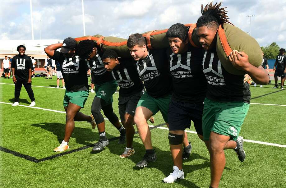 Spring seniors Nygzel Douglas, from right, Aristotle Marquardt, Alec Antia, Dallas Reid, Jaheem Davis and P.J. Smith compete in the Worm Carry during the War Zone Lineman Challenge at Spring High School on June 15, 2019. Photo: Jerry Baker, Houston Chronicle / Contributor / Houston Chronicle
