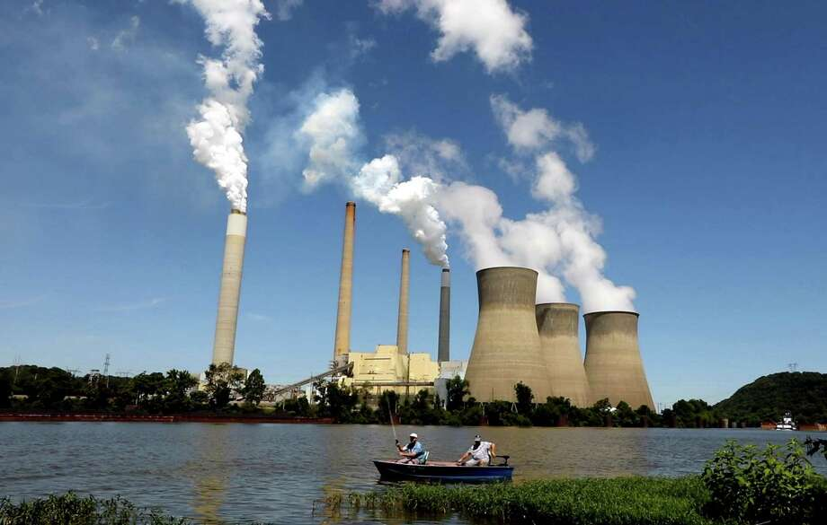 Fishermen drift by the John E. Amos coal-fired power plant operating on the banks of the Kanawha River near Winfield, W.V. (Carolyn Cole/Los Angeles Times/TNS) Photo: Carolyn Cole / TNS / Los Angeles Times
