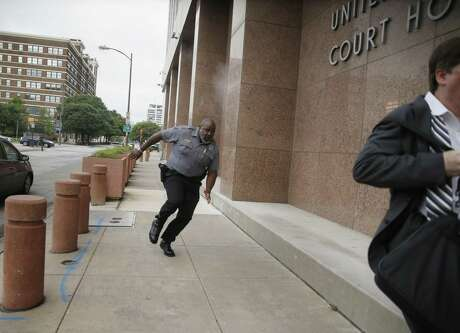A security guard and a civilian run for cover as bullets ricochet off the building as a shooter (far background left) fires toward them on Monday, June 17, 2019 at the Earle Cabell federal courthouse in Dallas. A masked gunman opened fire Monday at the federal courthouse before being fatally shot in an exchange of gunfire with federal officers, witnesses and authorities said. No officers or citizens were injured.