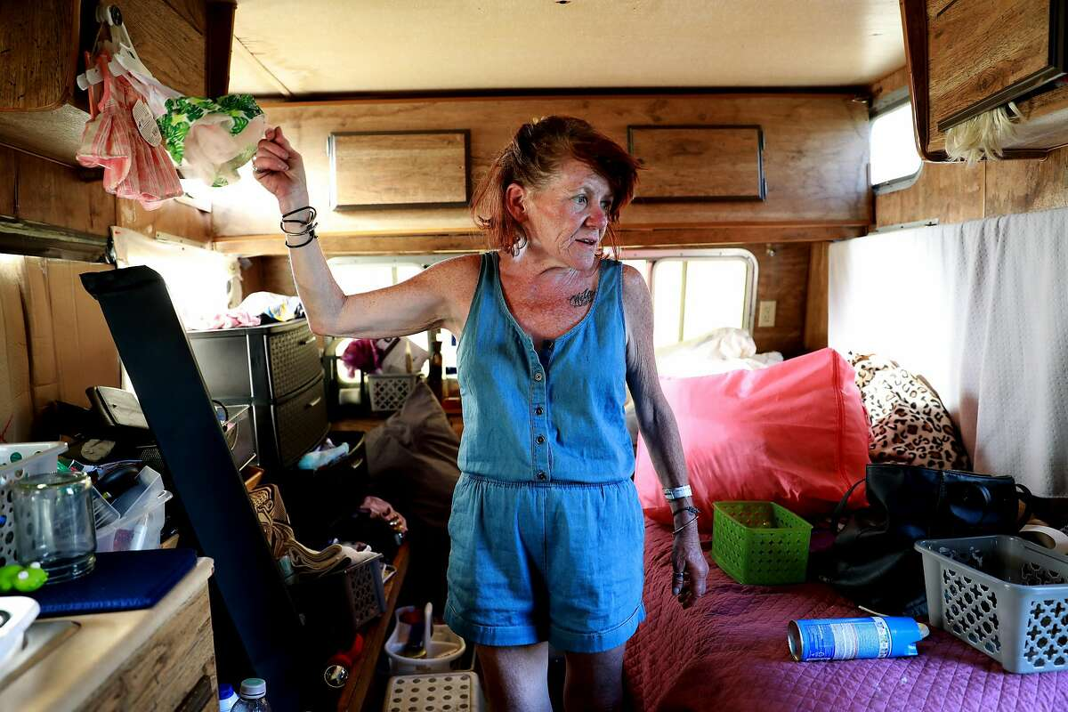 Eileen Mulcahy, 57, converses with a neighbor as she shows off clothes for her dog Chulita, 2, while inside her RV near 85th Ave. and Baldwin St. in Oakland, Calif., on Thursday, June 20, 2019.