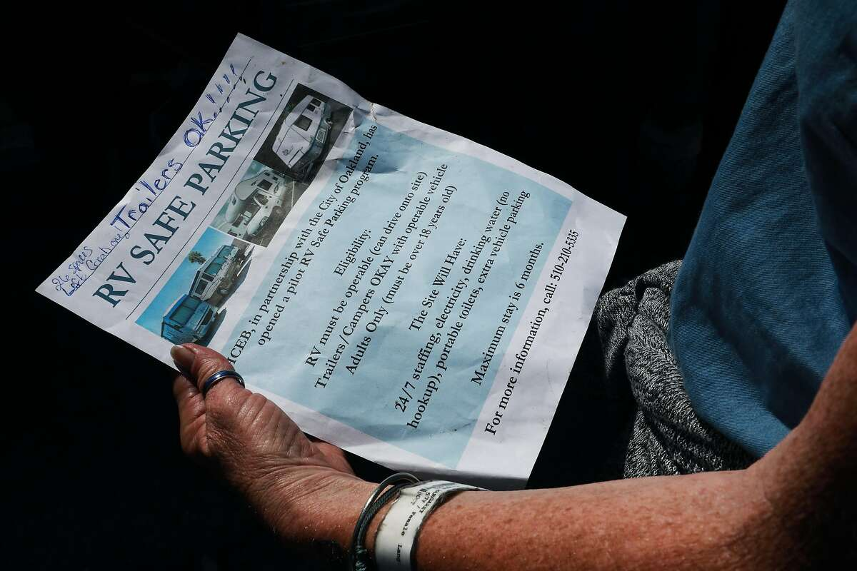 Eileen Mulcahy, 57, holds a flyer advertising a pilot RV Safe Parking Parking program, located at 771 71st. Ave., as she stands in front of her neighbor's RV near 85th Ave. and Baldwin St. in Oakland, Calif., on Thursday, June 20, 2019.
