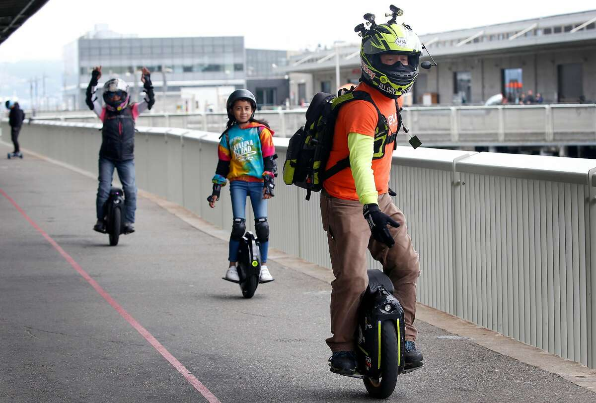 Jesse Garnier (right) departs Pier 15 with his wife Miles and their niece Alexis Villanueva, 11, aboard electric unicycles for a weekly 23-mile group ride by Bay Area Esk8 in San Francisco, Calif. on Saturday, June 15, 2019. Electric unicycles have become a popular mode of transportation.