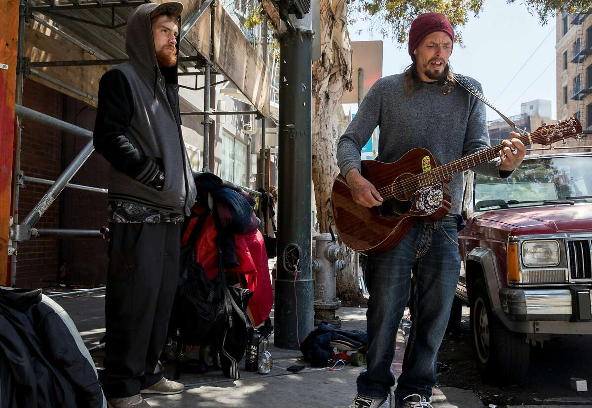 Fentanyl user Roger Boyd (right), 35, plays guitar while spending time with Shae, 30, on McAllister Street in the Tenderloin district of San Francisco, Calif. Friday, June 21, 2019.