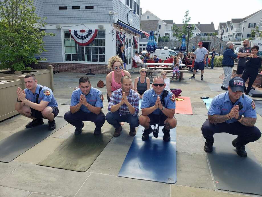 From left, firefighters Patrick Dailey and Paul Spennato, yoga instructor Donna Jackson, The Whelk co-owner Massimo Tullio, Lt. Todd Denke, and firefighter Kevin Mossop strike a yoga pose during the fundraiser for Turk Aksoy on June 21, 2019, in Westport. Photo: Liana Teixeira / Hearst Connecticut Media