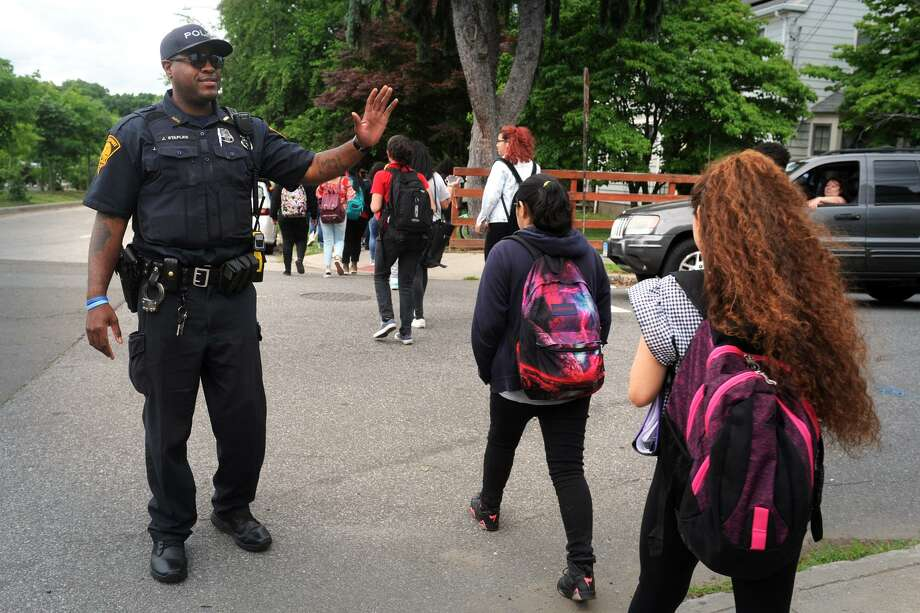 Bridgeport Police Officer John Staples, a school resource officer (SRO), greets students following as the leave Central High School at the end of their school day in Bridgeport, Conn. June 15, 2018. Photo: Ned Gerard / Hearst Connecticut Media / Connecticut Post