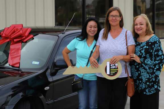 Suzanne Gilman (left) and Patricia Hudson with Cy-Fair Helping Hands stand with Teresa Weatherbee after gifting her a vehicle. Weatherbee has been without a car for six months and has had to walk everywhere or ask for rides ever since.