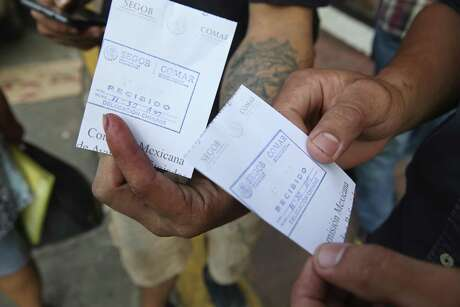 Migrants show their appointment details in front of the Mexican Commission of Assistance to Refugees, (COMAR), in Tapachula, Mexico, Monday, June 17, 2019. Hundreds of mostly Central American migrants line up early in hopes of securing an appointment to plea their case for a humanitarian visa.