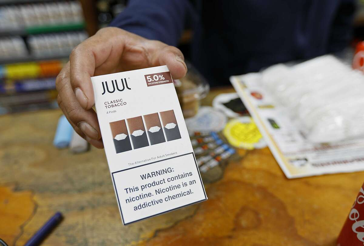 In this Monday, June 17, 2019, photo, a cashier displays a packet of tobacco-flavored Juul pods at a store in San Francisco.