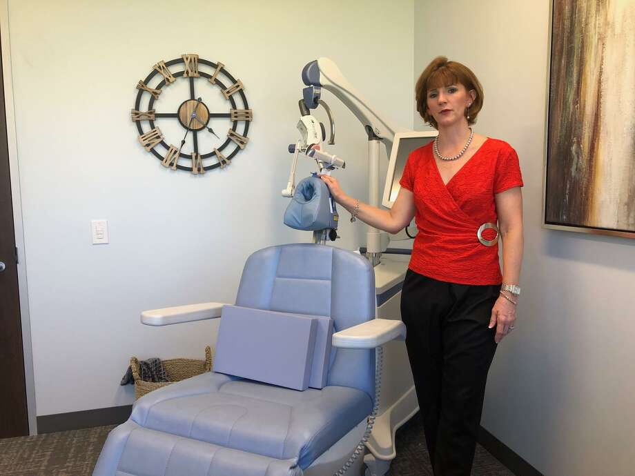 Dr. Kimberly Cress, MD, and the device she uses in her Katy psychiatric practice for Transcranial Magnetic Stimulation, a treatment for clinical depression. Photo: Mike Glenn / Staff Photo