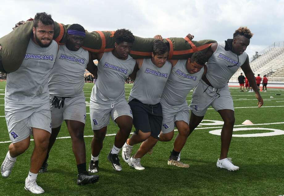 Klein Cain linemen Brayden Espinosa (12th), from left, Thomas Hines (11th), Damari Brooks (10th), Manny Navarro (11th), Johrdan Howard (11th), and Cedric Melton (12th), compete in the Worm Carry during the War Zone Lineman Challenge at Spring High School on June 15, 2019. Photo: Jerry Baker, Houston Chronicle / Contributor / Houston Chronicle