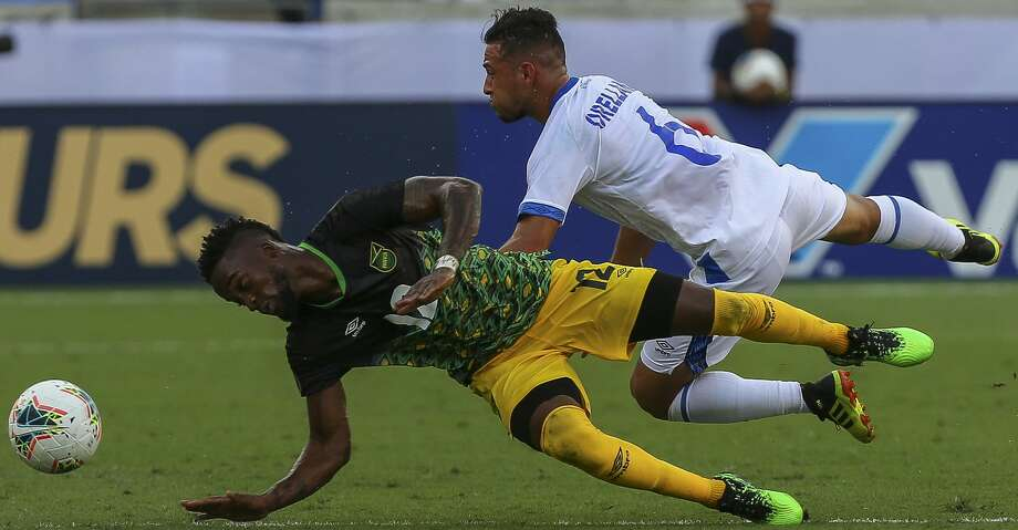 Jamaica forward Junior Flemmings (12) and  El Salvador midfielder Narciso Orellana (6) fall after battling to header the ball during the first half of the Group C match of the CONCACAF Gold Cup at BBVA Stadium Friday, June 21, 2019, in Houston. Photo: Godofredo A Vásquez/Staff Photographer