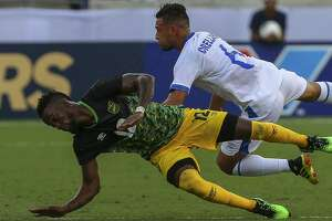 Jamaica forward Junior Flemmings (12) and  El Salvador midfielder Narciso Orellana (6) fall after battling to header the ball during the first half of the Group C match of the CONCACAF Gold Cup at BBVA Stadium Friday, June 21, 2019, in Houston.