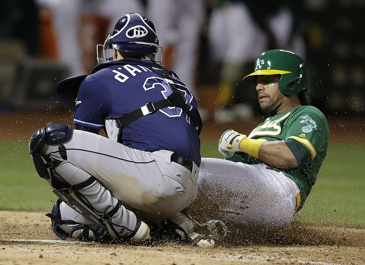 Tampa Bay Rays catcher Travis d'Arnaud, left, tags out Oakland Athletics' Khris Davis during the sixth inning of a baseball game Friday, June 21, 2019, in Oakland, Calif. (AP Photo/Ben Margot)