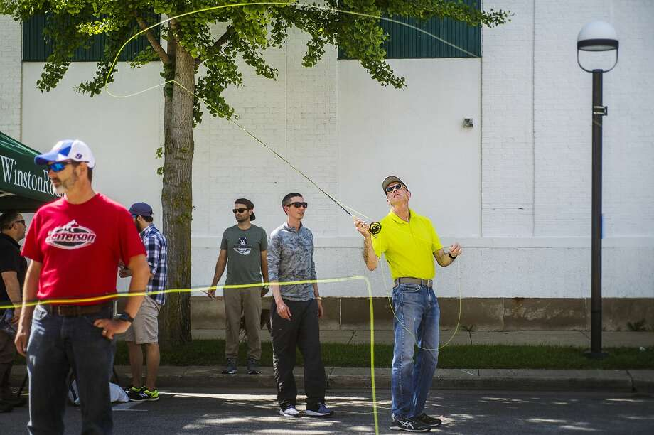 Bob Hobohm of Midland tries out a fly fishing rod during the second annual Outlandish fest on Friday, June 21, 2019 in downtown Midland. (Katy Kildee/kkildee@mdn.net) Photo: (Katy Kildee/kkildee@mdn.net)