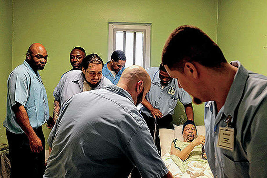 Participants in the Shawnee Hospice/Adult Comfort Care Program help move Ernest Carnes for a portrait at the Shawnee Correctional Center near Vienna. Photo: Isaac Smith | The Southern Illinoisan (AP)
