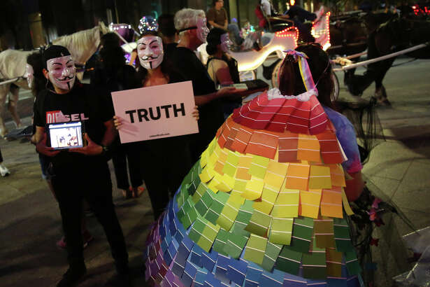Cristina Treviño walks by members of Anonymous for the Voiceless while carrying a rainbow design by Yahaira Dehill following the 10th Annual Rainbow on the Green atDiscovery Green Conservancy in Houston, Friday, June 21, 2019.