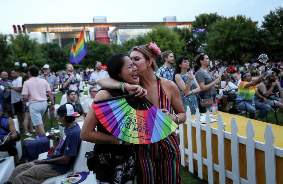 "Alana Delarosa sings along to a drag performer as her girlfriend, Nicole Pope, kisses her during a Pride event at Discovery Green on Friday, June 21, 2019, in Houston. ""It's being able to love whoever you want visibly and proudly,"" Pope said of Pride festivities. Photo: Jon Shapley, Staff Photographer / © 2019 Houston Chronicle"