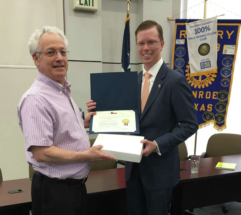 Pictured are Rotary Club of Conroe President Leland Dushkin, left, and State Rep. Will Metcalf, right. At Tuesday's Rotary meeting, Metcalf presented Dushkin with a state flag that flew over the State Capitol on June 11. Dushkin accepted the flag on behalf of the club. Photo: Photo By Sondra Hernandez