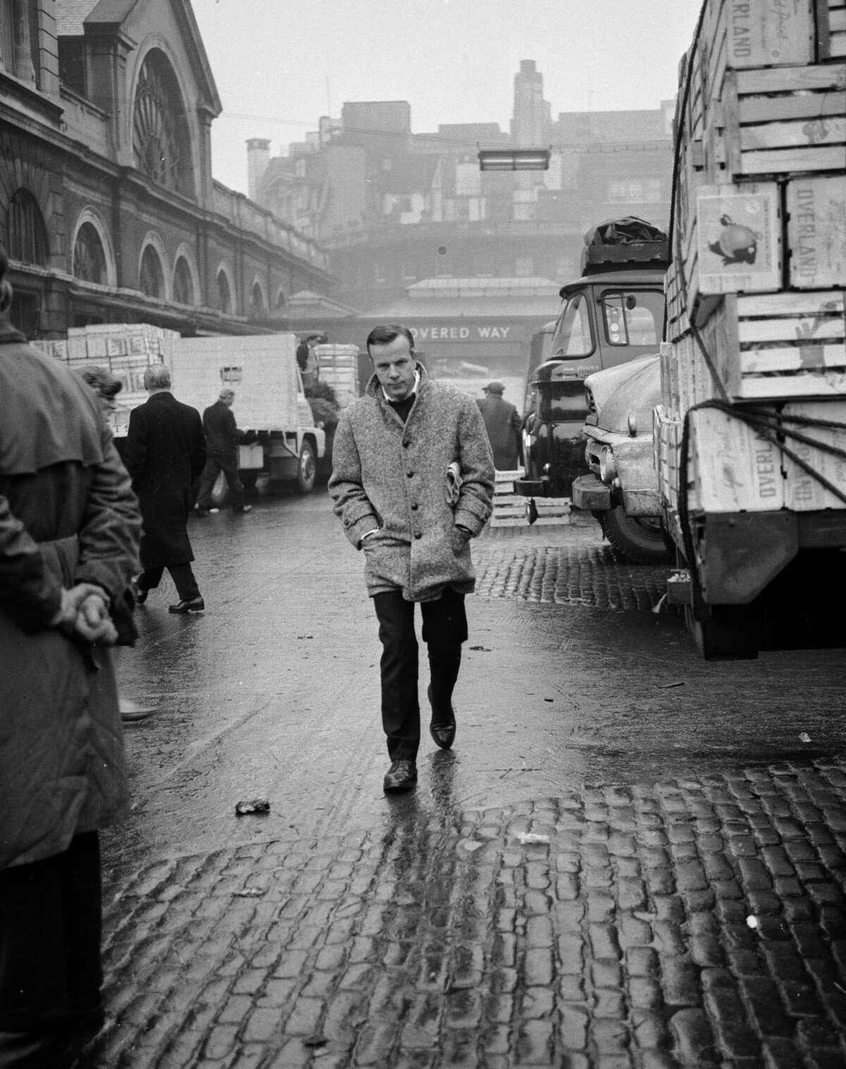 Italian conductor and film director Franco Zeffirelli, walking alone through Covent Garden market in London, January, 1964.