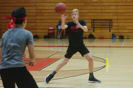 Luis Rodriguez (left) and Sam Thompson participate in a passing drill at the Clear Brook summer basketball camp.