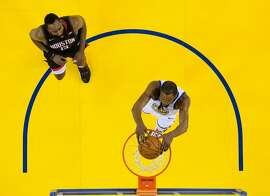 Kevin Durant (35) dunks ahead of James Harden (13) in the first half as the Golden State Warriors played the Houston Rockets in Game 5 of the Western Conference Semifinals at Oracle Arena in Oakland, Calif., on Wednesday, May 8, 2019.