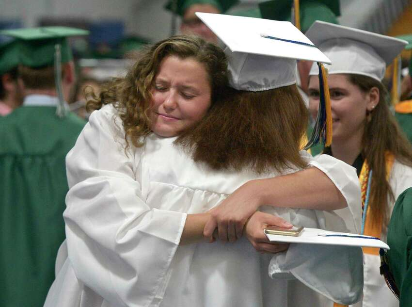 Elena Elizabeth Harcken gives a hug to class mate Hannah Estelle Kenny before the start of the New Milford High School Class of 2019 Commencement, Saturday, June 22, 2019, at the O'Neill Center, Western Connecticut State University, Danbury, Conn.