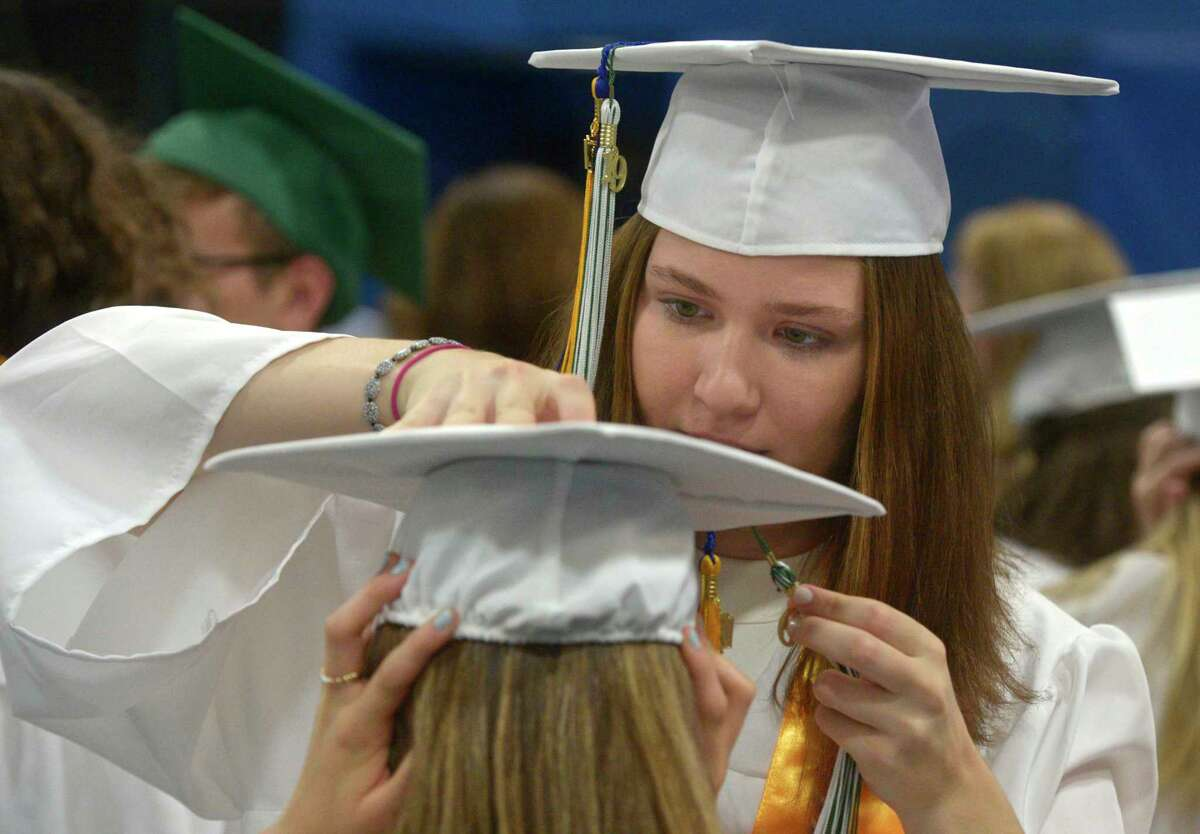 Hannah Estelle Kenny helps Madeline Olivia de la Parra with her tassel before the start of the New Milford High School Class of 2019 Commencement, Saturday, June 22, 2019, at the O'Neill Center, Western Connecticut State University, Danbury, Conn.