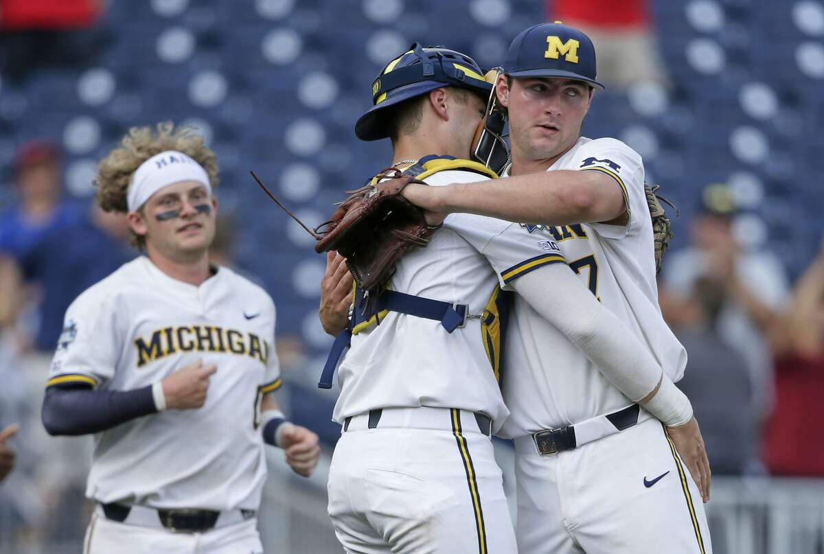 Michigan closing pitcher Jeff Criswell, right, is hugged by catcher Joe Donovan following an NCAA College World Series baseball elimination game against Texas Tech in Omaha, Neb., Friday, June 21, 2019. Michigan won 15-3. (AP Photo/Nati Harnik)