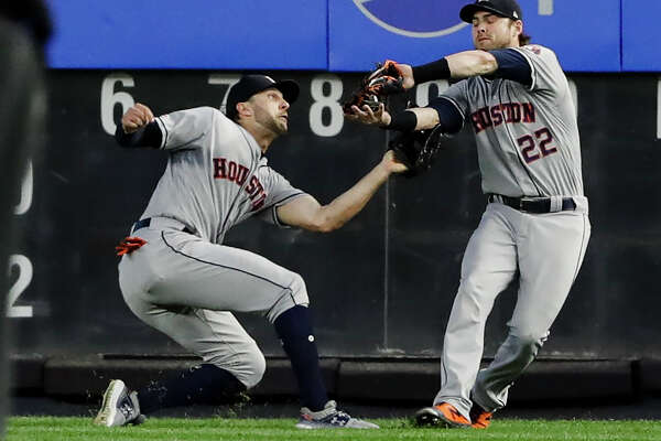 Houston Astros right fielder Josh Reddick (22) and center fielder Jake Marisnick collide as Reddick makes the catch for the out on New York Yankees' Austin Romine to end the fifth inning of a baseball game Saturday, June 22, 2019, in New York. (AP Photo/Frank Franklin II)