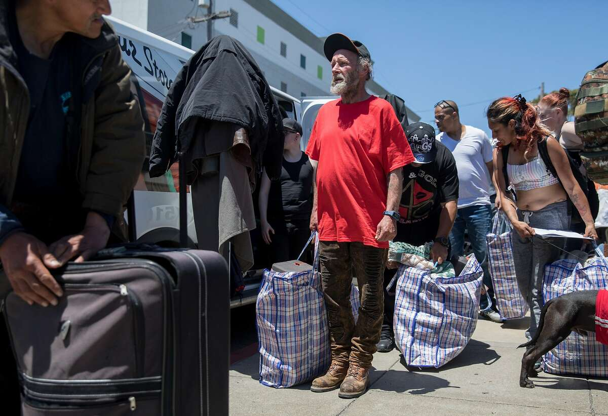 Unhoused resident David Chaplin joins others in receiving a care package during a protest highlighting San Francisco Department of Public Works' controversial practice of street sweeping and property confiscation held outside of San Francisco Department of Public Works yard in San Francisco, Calif. Friday, June 21, 2019.