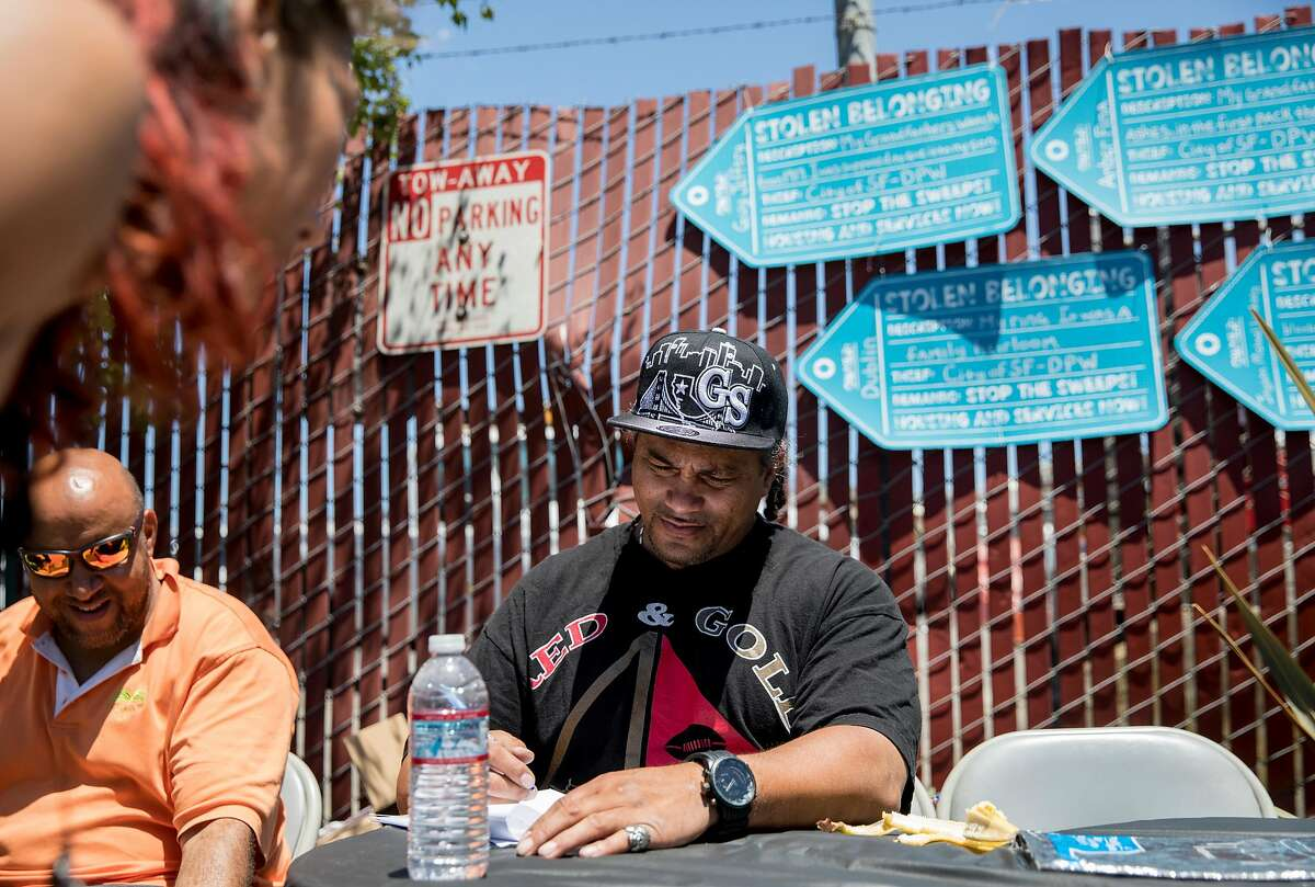 Unhoused resident Tyrone Shingledecker fills out a form identifying belongings taken from him by San Francisco's Department of Public Works including precious family jewelry during a protest highlighting San Francisco Department of Public Works' controversial practice of street sweeping and property confiscation held outside of San Francisco Department of Public Works yard in San Francisco, Calif. Friday, June 21, 2019.