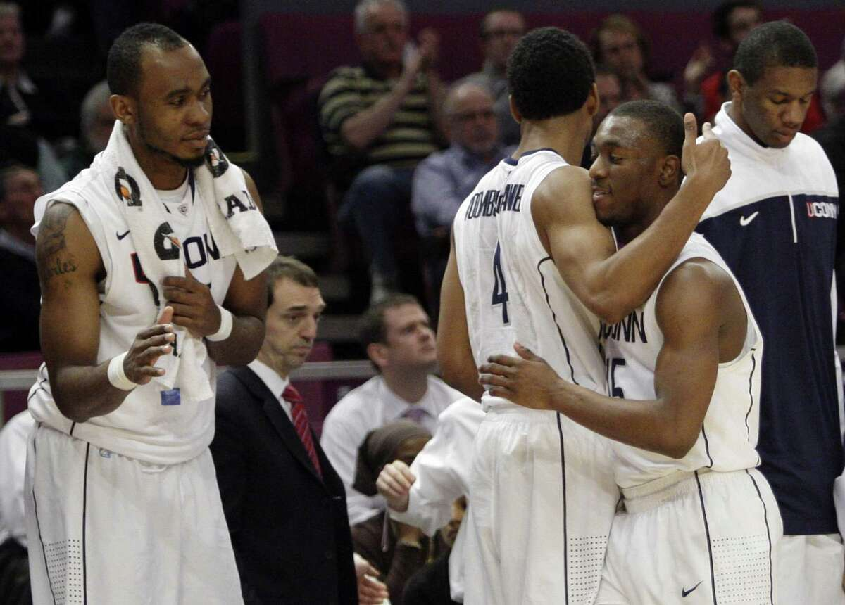 Connecticut's Kemba Walker, right, is congratuled by teammates Jamal Coombs-McDaniel (4) and Charles Okwandu, left, during the second half of an NCAA college basketball game against DePaul at the Big East Championship, Tuesday, March 8, 2011 at Madison Square Garden in New York. Walker scored 26 points in their 97-71 win. (AP Photo/Mary Altaffer)