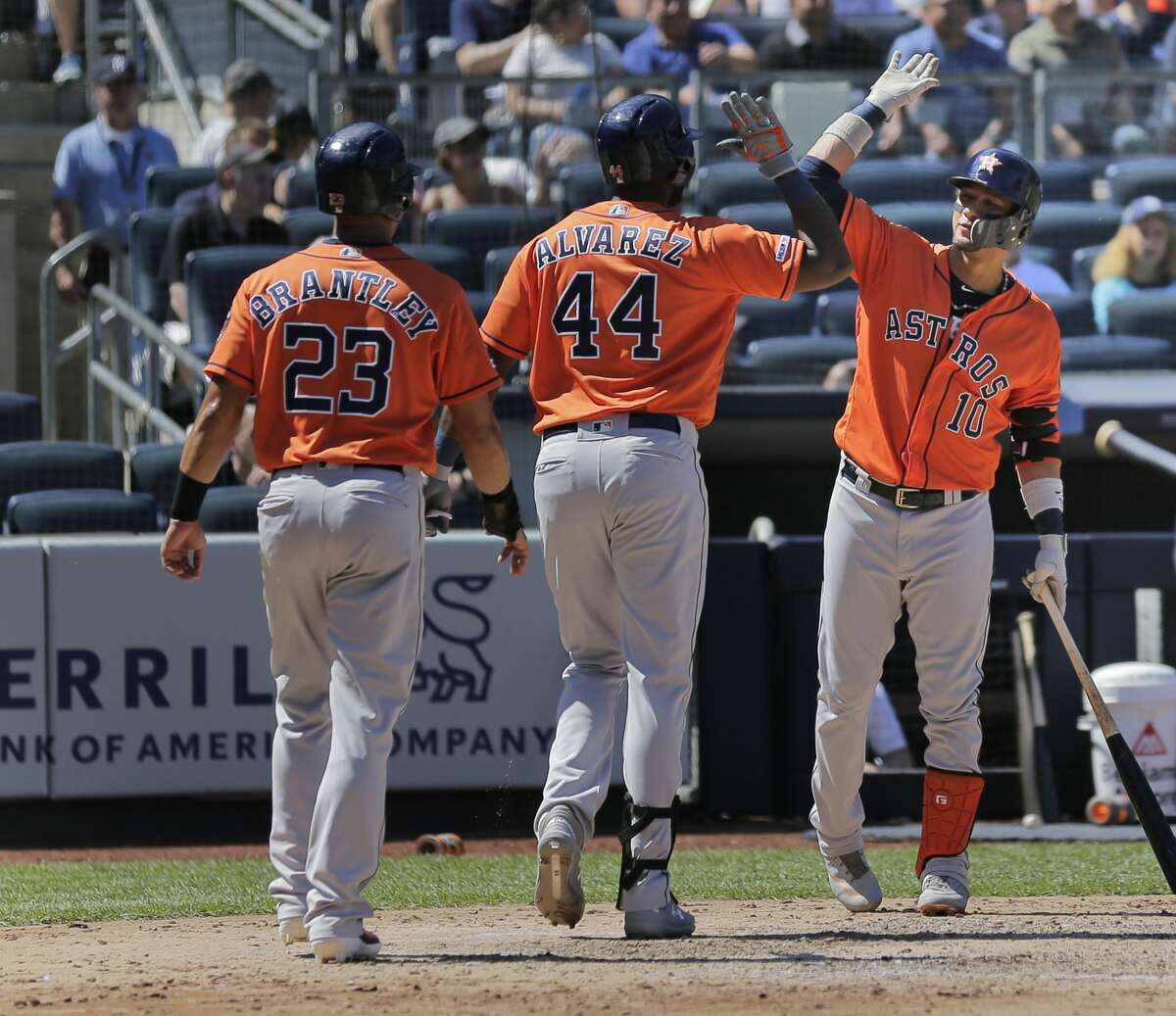 Houston Astros' Yordan Alvarez, center, celebrates his two-run home run with Yuli Gurriel, right, and Michael Brantley (23) during the fifth inning of a baseball game against the New York Yankees at Yankee Stadium, Sunday, June 23, 2019, in New York. (AP Photo/Seth Wenig)