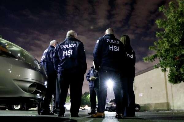 ARCHIVO- Agentes de ICE se reúnen antes de realizar una auditoría de empleo a un establecimiento 7-Eleven en Los Ángeles el 10 de enero de 2018.
